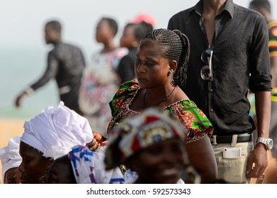 OUIDAH, BENIN - Jan 10, 2017: Unidentified Beninese woman with braids wears colored clothes at the voodoo festival, which is anually celebrated on January, 10th.