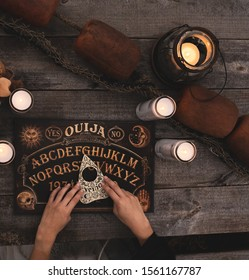 Ouija Board with candles. Seance on picnic table.