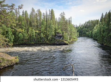 Oulanka river and the fast-moving rapids at the Oulanka National Park in Kuusamo, Finland. Green forest framing the flowing water. Beautiful, sunny summer day for hiking.
