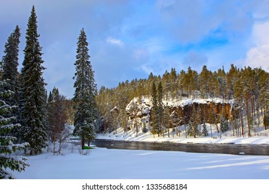 Oulanka river surrounded by forests and red cliffs in Oulanka wildlife reserve in winter, view from hiking trail.