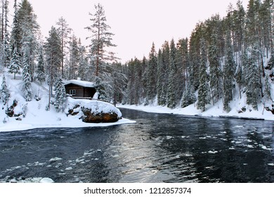 Oulanka river in winter evening with rest cabin on hiking trail ( in Oulanka nature reserve in Finland).