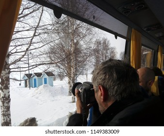 OULU, FINLAND - APRIL 11, 2018: Photographer taking pictures of the Nallikari beach through the tour bus window.