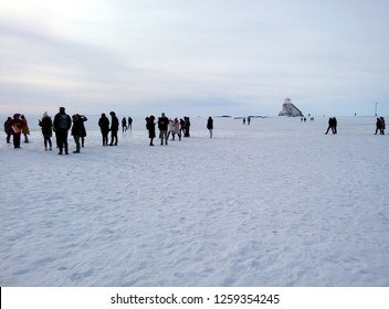 OULU, FINLAND - APRIL 11, 2018: Tourists walking towards the lighthouse on the frozen Baltic Sea and the snow-covered Nallikari beach in Oulu, Finland.