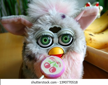 OULU, FINLAND - APRIL 8, 2019: Furby 1998 Leopard With Green Eyes Eating A Lollipop