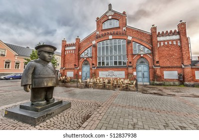 OULU, FINLAND - JULY 06, 2016:  Market Square, located in front of the Market Hall with Policeman statue (Toripolliisi) by Kaarlo Mikkonen. Oulu, Finland.