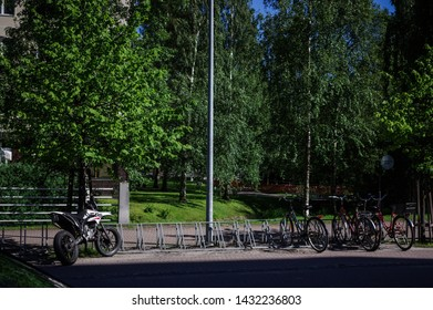 Oulu, Finland - July 11, 2016: Off-road motorcycle and bicycles parked on the street with green trees and grass as background in Oulu, Finland