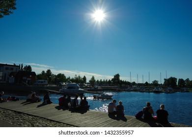 Oulu, Finland — July 11 2016: People enjoying sunshine near the port in Oulu city center in polar day
