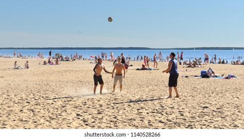 OULU, FINLAND - JULY 11, 2018: Tourists play ball on Nallikari beach. Heat
