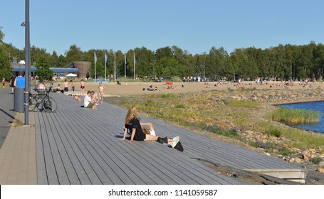 OULU, FINLAND - JULY 11, 2018: People on Nallikari beach. Residents of Oulu are happy with hot weather