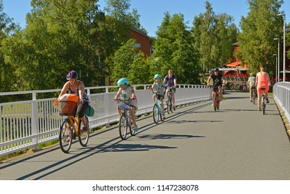 OULU, FINLAND - JULY 11, 2018: Pedestrian bridge across river Oulujoki. Cyclists