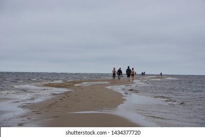 Oulu, Finland - July 16 2016: People walking on long sandbanks at Kalajoki near Oulu in a cloudy summer day