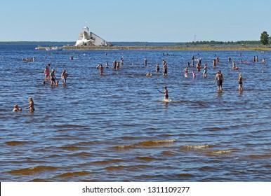 OULU, FINLAND - JULY 17, 2018: People swim in background of lighthouse Majakka. Nallikari beach in Oulu