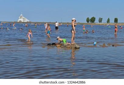 OULU, FINLAND - JULY 17, 2018: Happy people on background of lighthouse Majakka. Nallikari in Oulu, Suomi
