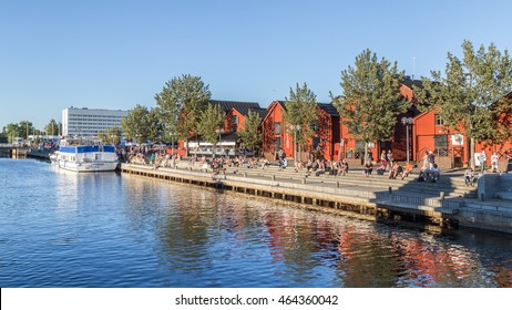 OULU, FINLAND - JULY 21, 2016:  People sitting along the harbor in the center of OULU Finalnd enjoying an exceptional sunny and hot evening.
