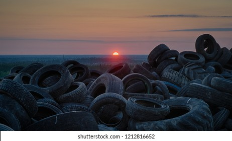 OULU, FINLAND - JUNE 23, 2013: An image of piles of old used tires in a landfill at sunrise