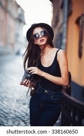 oung beautiful brunette girl in a hat, sunglasses, t-shirt and jeans with a film camera in hand walks along the ancient city