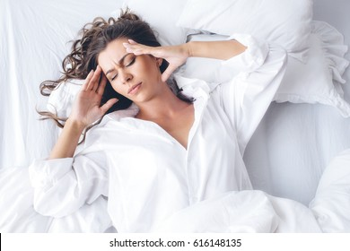 oung beautiful Caucasian woman in the morning lying on a white bed in a white shirt, having a headache / insomnia / migraine / stress