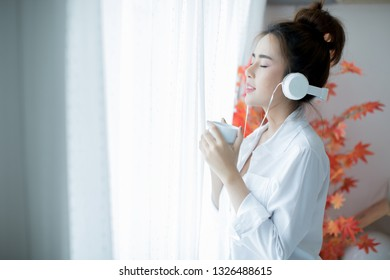 oung beautiful woman in bright outfit enjoying the music at home
