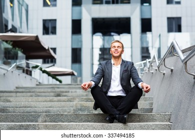 oung businessman sitting on the steps of the office and meditates
