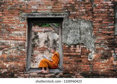 oung novice monk reading a book. Novice monk learning in temple, Ayutthaya province, Thailand