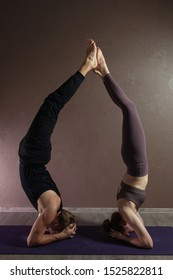 oung sporty man and girl practicing yoga, meditating in yoga pose, working out, wearing sportswear, indoor full length, brown yoga studio