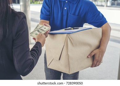 oung woman pay money and receiving parcels from courier