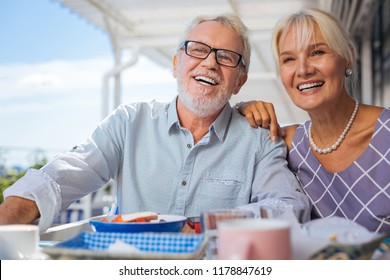 Our best friends. Happy elderly couple smiling while looking at their friends
