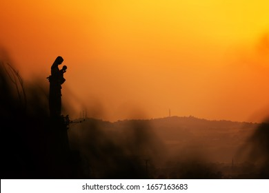 Our blessed virgin Mary, with her son in her arms, prays for sinners, against the light, against a background of sunset lights.