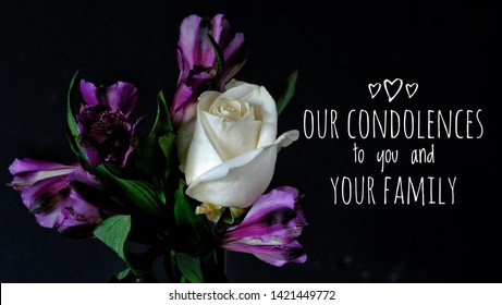 Our Condolences to you and your Family sympathy card. One white rose and deep purple flowers on black background beside sympathy message