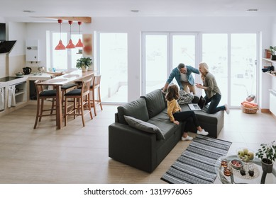 Our cozy apartment. Cute little girl sitting on couch with laptop and looking at parents while they smiling