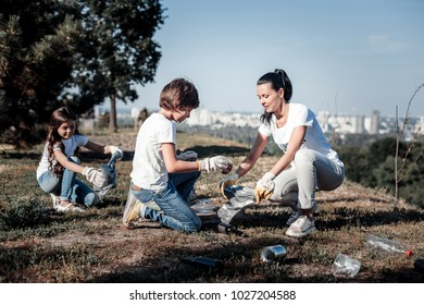 Our environment. Nice pleasant smart children sitting and collecting garbage while helping the environment