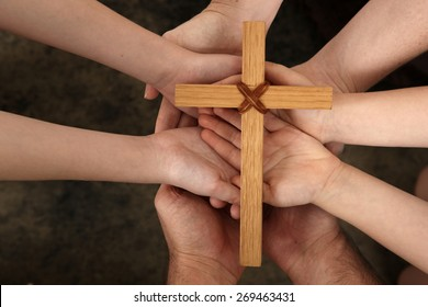 Our Faith - family hands holding cross