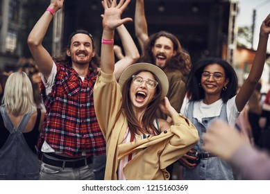 Our favorite song. Waist up portrait of young stylish people raising hands and smiling