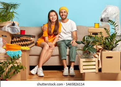 Our first home. Newlywed couple bring boxes with belongings in new apartment, hug and sit on sofa, start new life in recently bought flat, smile at camera make plans for future live apart from parents