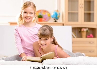 Our hobby. Pleasant happy little sisters smiling and reading book while lying on bed