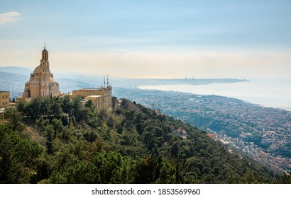 Our Lady of Lebanon Maronite church sits on a hill over the Jounieh bay, with Beirut capital city in the background, in Lebanon, Middle East