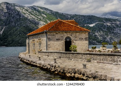Our Lady of the Rock Island and Church near Perast on shore of Boka Kotor bay (Boka Kotorska), Montenegro, Europe.