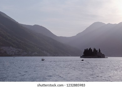 Our Lady of the Rock and St.George Island in Perast on shore of Boka Kotor bay, Adriatic Sea, Montenegro. Picturesque sea and mountain scenery during Fashinada (Fasinada) -  is an ancient folk holiday