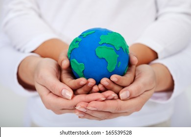 Our legacy to the next generations - a clean environment, with child and adult hands holding earth globe