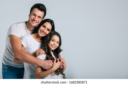Our life! Beautiful excited and the funny family team is posing in a white t-shirt while they isolated on white background in studio.