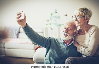 Our life is full of memories. Senior couple taking self portrait together at home. Space for copy.