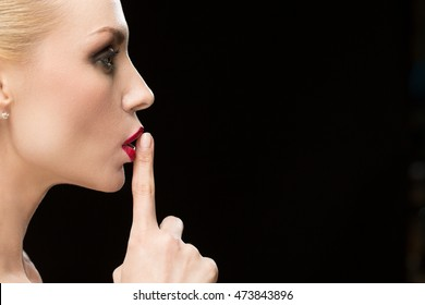 Our little secret. Closeup portrait of a profile of a stunning beautiful red lipped woman shushing with her finger to her lips on black background copyspace on the side