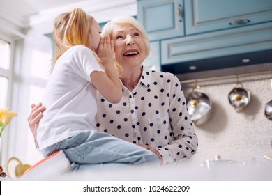 Our little secret. Pleasant charming elderly woman hugging her little granddaughter and listening to her secret while the girl sitting on the kitchen counter and whispering into her ear