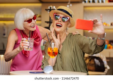 Our photo. Pleasant good looking woman taking a selfie while sitting together with her friend