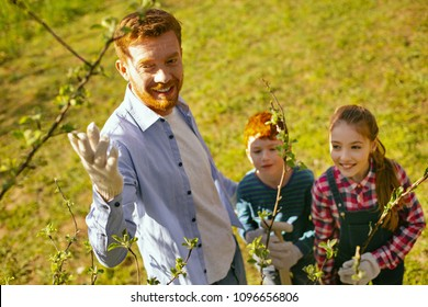 Our planet. Happy delighted man pointing at the trees while telling his children about the planet