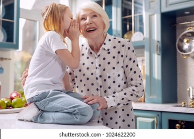 Our secret. Adorable little girl sitting on the kitchen counter and whispering in her grandmothers ear while the woman listening attentively and smiling