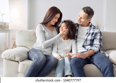 Our treasure. Attractive alert curly-haired girl smiling and sitting on the couch with her parents and they looking at her