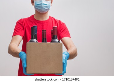 ourier wearing protective mask and gloves holding box with bottles of wine. Safe online wine store delivery during quarantine.