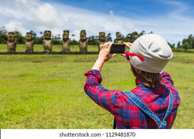 ourist young woman doing photo near Moai statues in the Rano Raraku Volcano in Easter Island, Chile