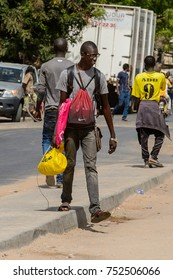 OUSSOUYE, SENEGAL - APR 30, 2017: Unidentified Senegalese man carries a backpack in Oussouye, a town in Senegal